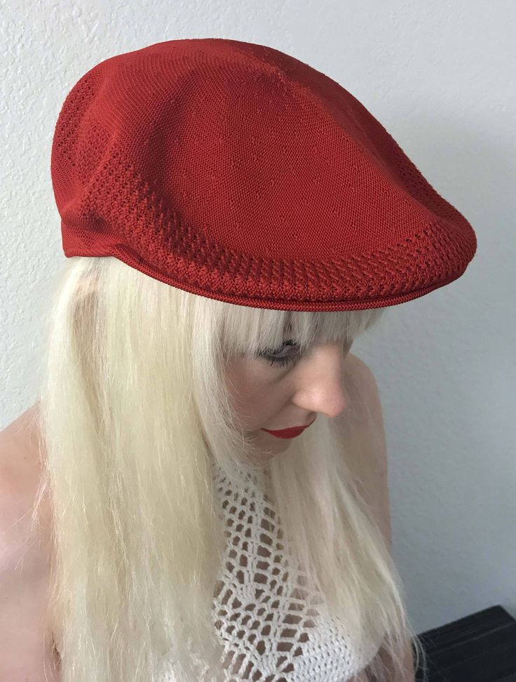 A bright red vintage beret, newsboy, cabbies hat, golf hat, drivers cap, manufactured in England by Kangol. This iconic Kangol classic, with the Ventair pattern around the outer edge, the 504 Ventair Cap has remained fresh since it was introduced in the early 80s. The 504 cap gets its name from the number assigned to the original block shape on which it was made. Tropic yarn is Kangols traditional polyester blend, and is a warm weather yarn that has been a staple in the collection since the…