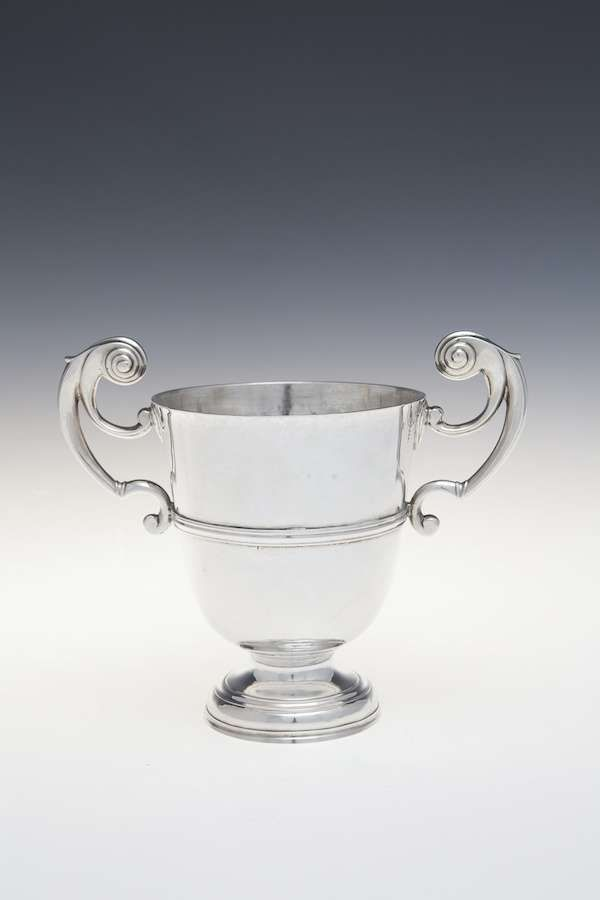 AN IRISH GEORGE II/GEORGE III PROVINCIAL SILVER TWO HANDLE LOVING CUP, Cork circa 1750-1760, mark of John Irish, plain with twin handles and central reeded girdle, raised on a stepped pedestal foot (c.22.5ozs). 13.5cm diameter, 23cm wide over handles, 19cm high
