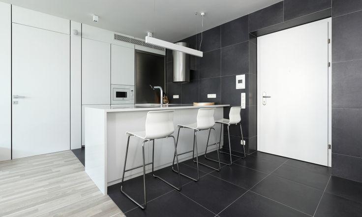 Biela kuchyňa apartmánu na prenájom tvorí súčasť denného priestoru, preto sme si na jej dizajne dali záležať. Pracovná doska s drezom z bieleho umelého kameňa a matne biele dvierka sme pre dokonalosť doplnili bielymi kuchynskými spotrebičmi. V čisto bielej kuchyni vynikajú nerezové doplnky - digestor a roletka.