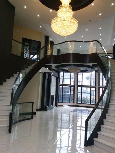 Une rambarde d'escalier en verre thermoformé courbé réalisée par Verre Design/ A glass rail done by Verre Design