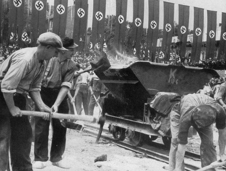 Nach der Grundsteinlegung zum Haus des Fremdenverkehrs in Berlin am 14 Juni 1938 am Runden Platz durch den Führer beginnen unter dem Gesang des Deutschlandliedes die Bauarbeiter auf 16 Baustellen zugleich mit Ihrer Arbeit, die das neue Berlin schaffen wird.