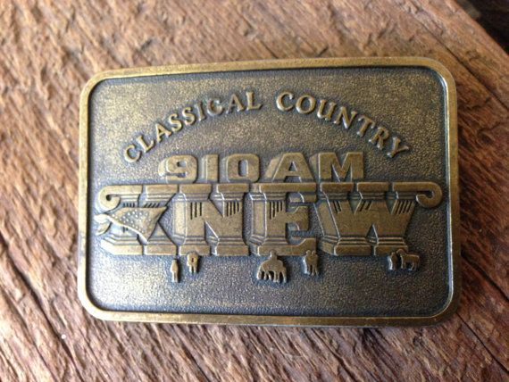 KNEW 910 AM radio played country music in Northern California from the mid 1970s until the late 90s. This solid brass buckle celebrates the stations Classical Country heyday with a monumental logo. Dressed in a bandanna, it rises above a plain dotted with tiny people and horses like some crazy country music Parthenon. Its in terrific shape, with the deep, warm patina only old brass can deliver.  3W x 2H; takes a belt up to 1 3/4W.    SHIPPING NOTE: I generally ship via standard USPS within…