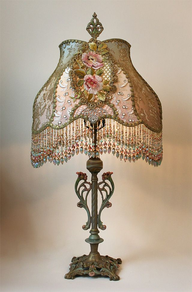 Art Nouveau styled antique table lamp holds a Chateau style shade in soft tones of pale pink to celadon green. The hand beaded shade is covered in an assortment of antique ornate beaded and metallic laces and the center panels hold exceptional 19th Century French embroidered appliqués surrounded by gilded metallic trim. The lamp is romantic and elegant and lights up beautifully.