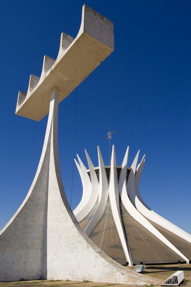 Clássicos da Arquitetura: Catedral de Brasília, D.F., Brasil. A catedral e o campanário, que ganhou uma concepção totalmente inovadora. O campanário é constituído por uma barra linear, que apoia sobre ela quatro sinos, sustentada por um único ponto central, que desce formando quatro pilares em suaves curvas. Os 4 grandes sinos foram doados pela Espanha. Arquitetura: Oscar Niemeyer.  Fotografia: Christoph Diewald no Flickr.