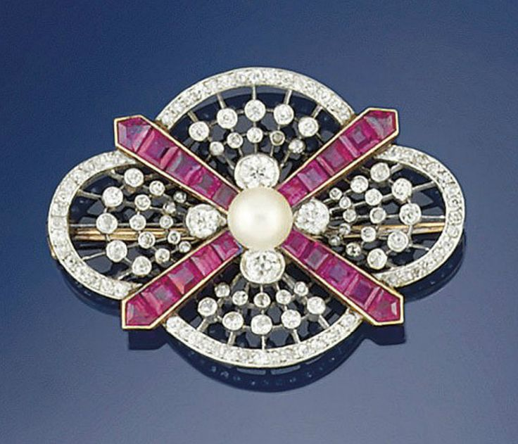 An Edwardian diamond and ruby brooch  Designed as a diamond pierced quatrefoil plaque with calibré ruby cross motif and bouton pearl centre, circa 1905