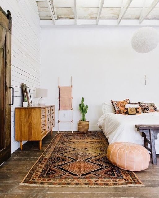 Bright And Airy Loft-Style Bedroom With Patterned Rug, Leather Pouf And Large Wooden Cabinet