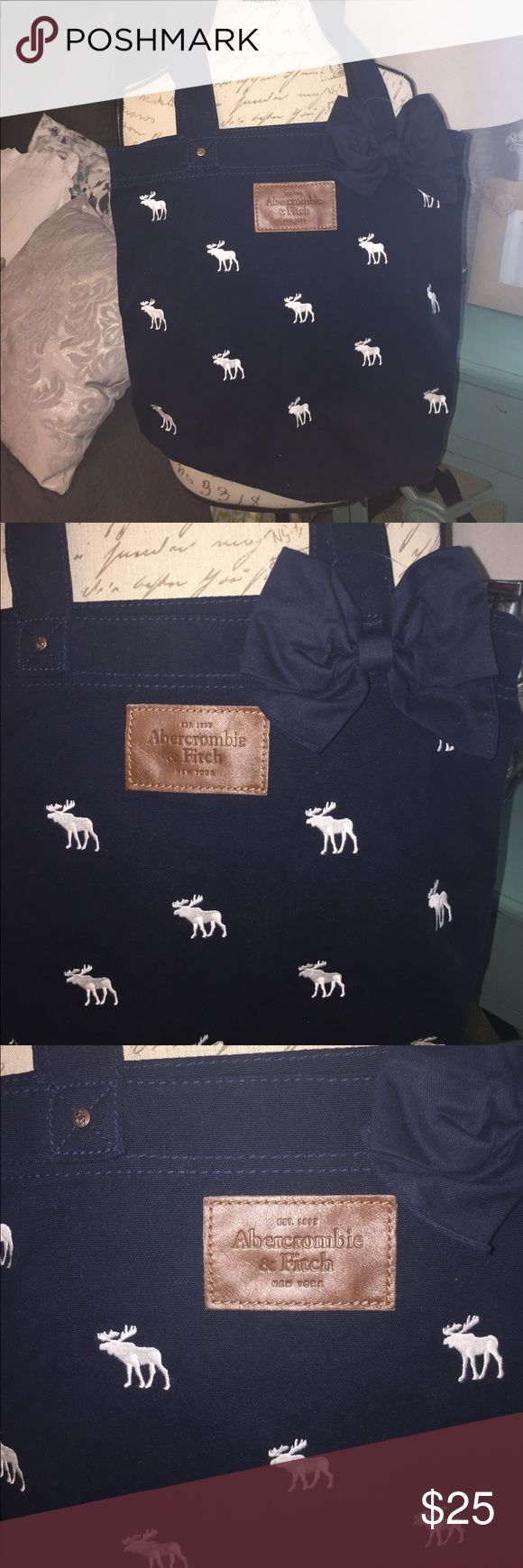 """Abercrombie & Fitch tote New without tags (still has the tag fastener) navy blue tote. Decorated with white embroidered Abercrombie moose all over and a big navy blue bow. Rivets are brushed silvertone stamped with the moose logo and the open rivets in the sides are stamped """"Abercrombie and fitch 1892"""" the front of the bag has a  brown leather patch that reads """" EST. 1892 Abercrombie & Fitch NEW YORK"""" has one side pocket inside. And reinforced handles. From a smoke free and pet free home…"""