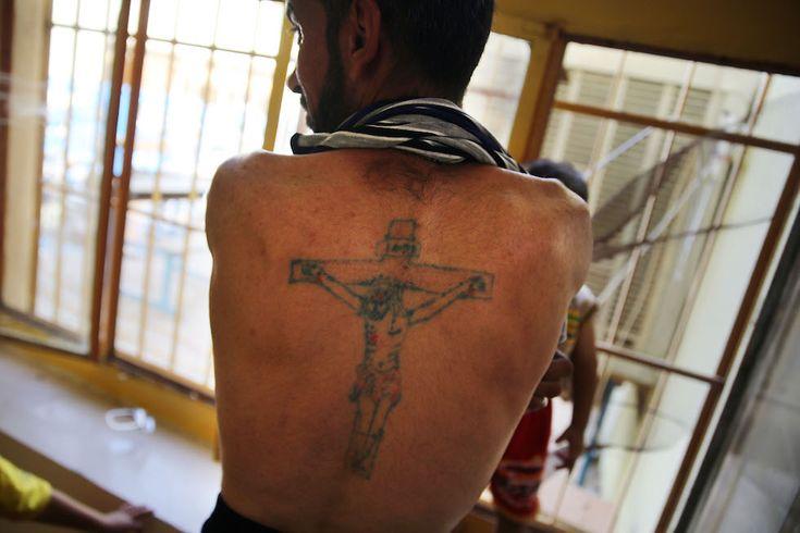 Quelli che scappano dall'Iraq Un iracheno cristiano mostra un tatuaggio con la crocifissione di Cristo nella chiesa di San Giuseppe, a Erbil, dove si sono rifugiati centinaia di cristiani fuggiti da Mosul, 27 giugno 2014. (Spencer Platt/Getty Images)