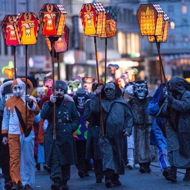 Degli uomini sfilano con delle lanterne per la processione del Carnevale di Basilea