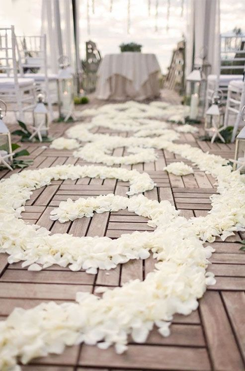 Flower petals, placed in an intricate design, mark the ceremony aisle for this couple's Big Day. Photo by We Heart Photography