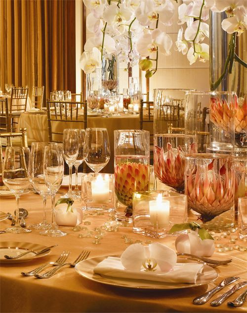 Beautiful blooms submerged in transparent vessels will magnify the size, contrast and colour. But not all flowers will be up to the task. Choose exotic flowers like protea which tend to be heartier. To complete the table, choose linens in a more neutral colour and add plenty of white candlelight to help further emphasize the centrepiece. To create additional drama, add a single bloom on each place setting, but ensure you use exotic flowers such as orchids, to match the centrepiece.
