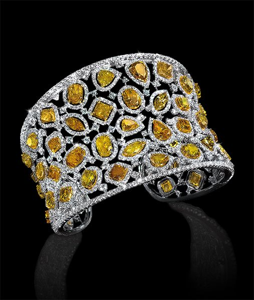 Fancy Yellow Diamond Cuff - 18-karat white gold cuff featuring various shades of of fancy yellow diamonds in an assortment of cuts framed with white diamonds. Cellini Jewelers.