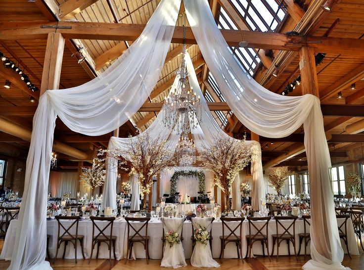 Head table decor features a low romantic collection of candlelight and fresh floral down the center of the table. Main feature of this decor are the tall and magnificent, natural curly willow trees accented with fresh white flowers set atop an illuminated mirror cube.