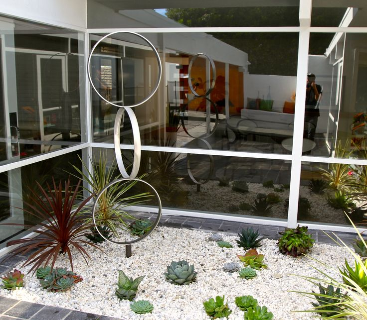 Some husbands give jewelry as anniversary gifts. Others...give sculpture. Stainless steel sculpture from TerraSculpture works beautifully in this mid-century modern home and atrium garden.