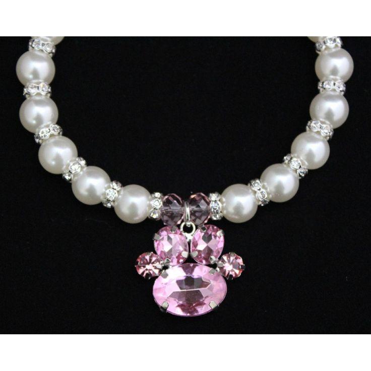 Superbe collier imitation de perle pour chien et animal de compagnie joliment ornée de pierre de strass et d'un joli pendentif en forme de patte. La chainette permet de jouer avec la longueur du collier. Ce bijou aura un chic fou au cou de votre animal.