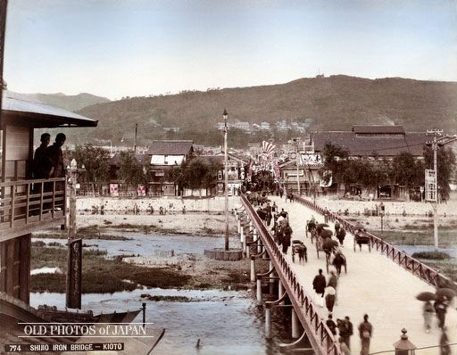 1890's, Kyoto. A view on Shijo Ohashi (Shijo Great Bridge), one of Kyoto's most important bridges on the river Kamogawa. Crossing the bridge and walking towards the mountains brought visitors to Yasaka Jinja, the shinto shrine that originated the famous Gion Matsuri. The road towards Yasaka Jinja is quite wide nowadays, but on this photo it is still narrow.