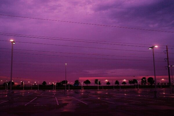 The parking lot was still slick from the storm as you cut across it under sprinkling rain. Although the worst of it was over, the sky's fat clouds were plum purple and ominous, casting a strange glow over the distant yellow lights of the store.