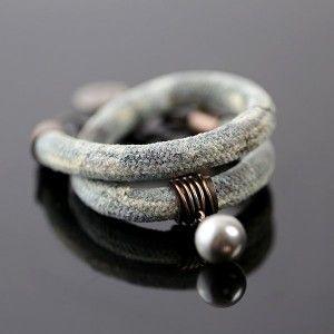 Niech Cię porwie orzeźwiający plusk kolorów!  Efektowna bransoleta zawijana na rękę, wykonana z miedzi, lnu i perły seashell*. Samodzielnie barwiony lniany sznur o popielato – błękitnych odcieniach ozdabia pierścień z wiszącą, srebrzystą perłą. Sznur został zakończony ręcznie wykonanymi końcówkami wraz z haczykowym zapięciem z regulacją. Na końcu regulacji widoczna zawieszka z naszą sygnaturą. Metale lutowane tradycyjnymi technikami jubilerskimi, powierzchnia miedzi została pokryta oksydą…