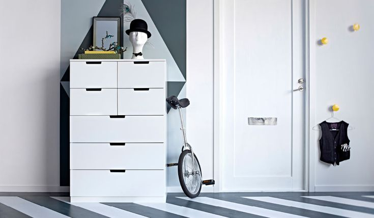 A hallway with a white chest of drawers with two yellow and five white drawers