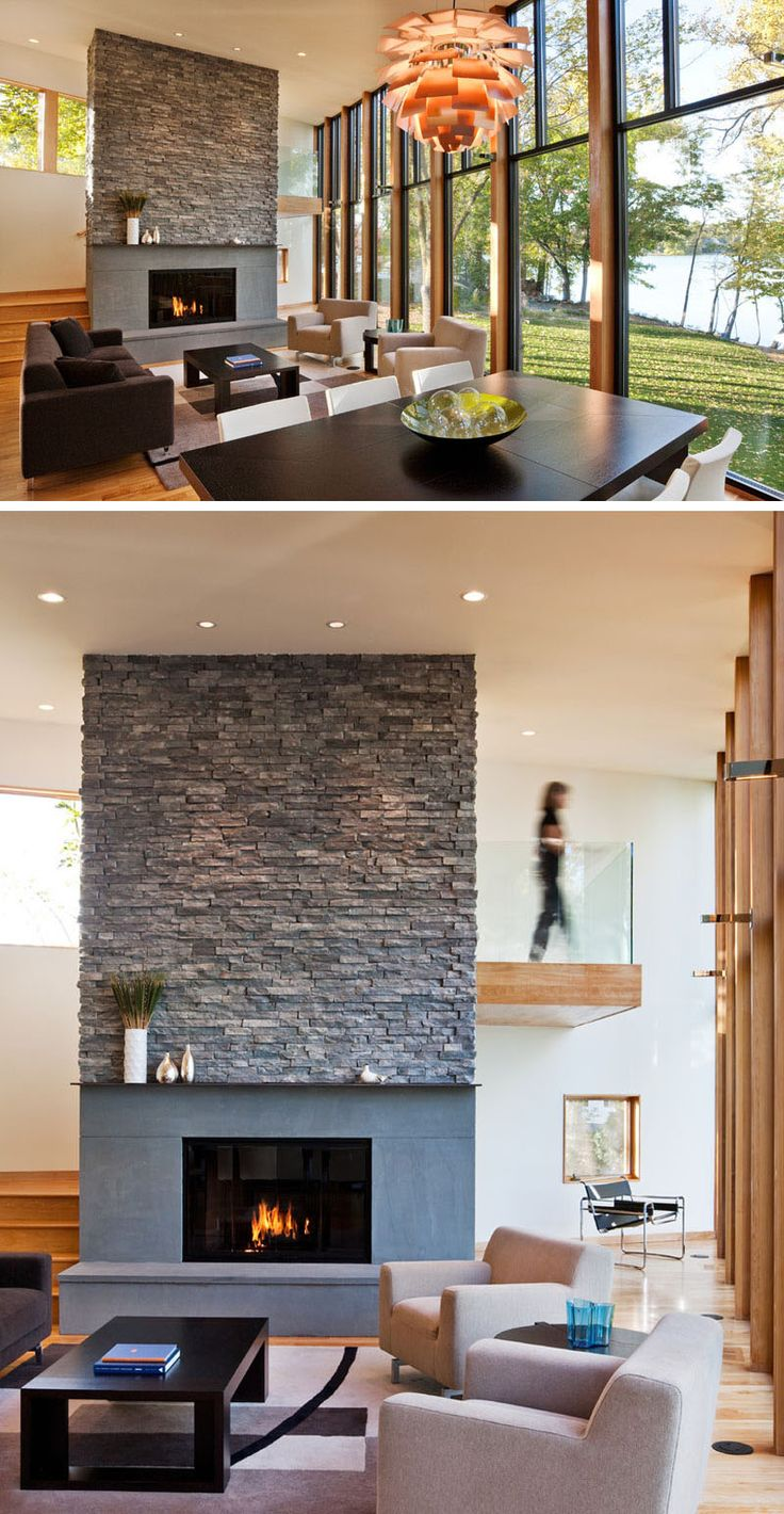 In this modern living room, a large gas fireplace covered in stone hides the staircase from view.