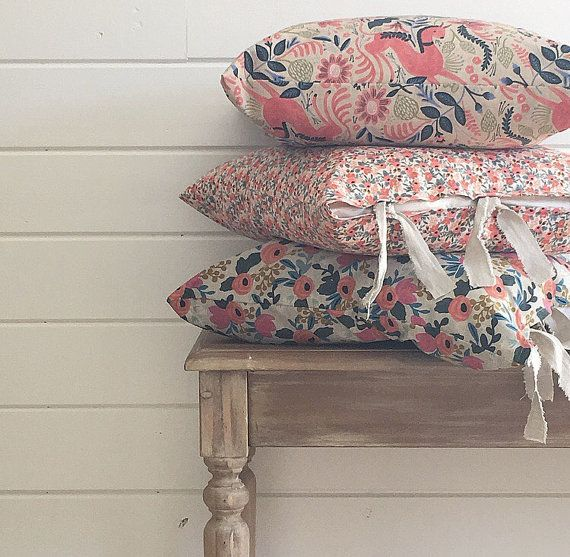 Our classic farmhouse pillows in stunning prints from the Rifle Paper Companys cotton and canvas fabric lines. Fabrics have exceptional feel and brilliant colors.  Pillows measure approx 20 square, and feature coordinating hand torn linen blend tie tops for casual charm.  Your choice of fabrics, as seen in photo number five, as follows: 1. Queen Anne - Peach (cotton) 2. Rosa Floral - Peach (cotton) 3. Rosa Floral - Navy (cotton) 4. Tapestry - Black (cotton) 5. Rosa - Natural (cotton/line...