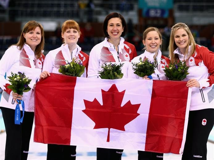 Olympic and world Ladies Curling gold medallists Jennifer Jones (R), Kaitlyn Lawes (2nd R), Jill Officer (C), Dawn McEwen (2nd L) and Kirsten Wall (L) of Canada celebrate during the flower ceremony for the Gold medal match between Sweden and Canada on day 14 of the Sochi 2014 Winter Olympics at Ice Cube Curling Center | Sochi 2014 Winter Olympics