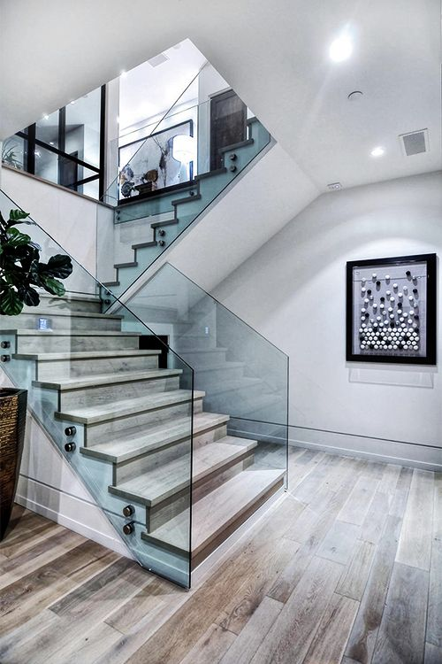 This bright and modern staircase is simple enough except for the wonderful use of glass as a means of a railing