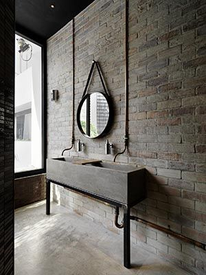 Concrete form double sink with exposed copper water line. Exposed grey brick wall | bathroom