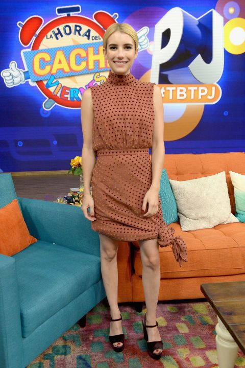 Emma Roberts wears a polka dot dress with a high neck, cinched waist, and knot at the hem on the set of Despierta America at Univision Studios in Miami on Thursday.