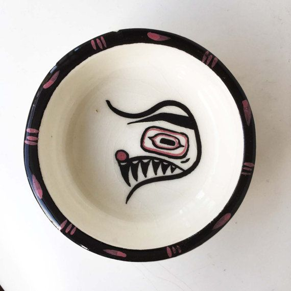 Designed by David Lambert (considered the 'god-father' of BC pottery industry, part-time teacher at Vancouver Art School, one of the originators of the BC Potters Guild). Featuring Haida designs of a Raven on the shot glass, and Houskana (The Fisherman) on the bowl.  Egg cup or shot glass is just over 2 inches high, and just under 2 inches across opening. Bowl is 3 1/4 inches across and 1 inch high. Both have crazing, but no chips or cracks.  Lambert Potteries was in operation from 1945-...