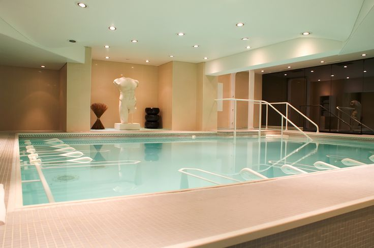 Grecian style indoor pool with statues and pot lighting