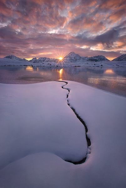 The solitary unfrozen line of a burried stream disappears into a frozen lake and the sunset beyond, photographed from a very remote lake on the North face of Jasper's Mount Fryatt, in Alberta. (c) Marc Adamusbeautiful planet earth