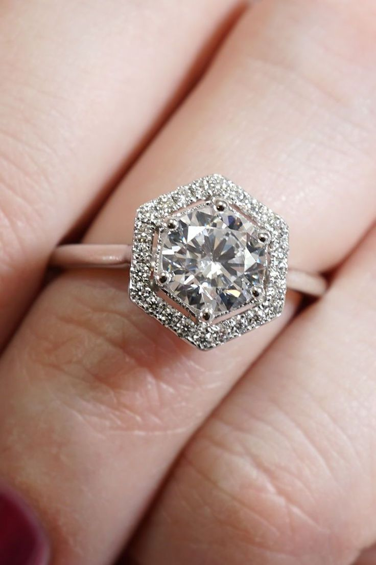 This stunning engagement ring features a round brilliant cut diamond prong set in the center of a hexagonal halo of split prong set diamonds, all of which is accented by milgrain beading around the center setting. Designed and created by Joseph Jewelry | Seattle, WA | Bellevue, WA | Online | Design Your Own Engagement Ring | #engagementring #UniqueEngagementRings