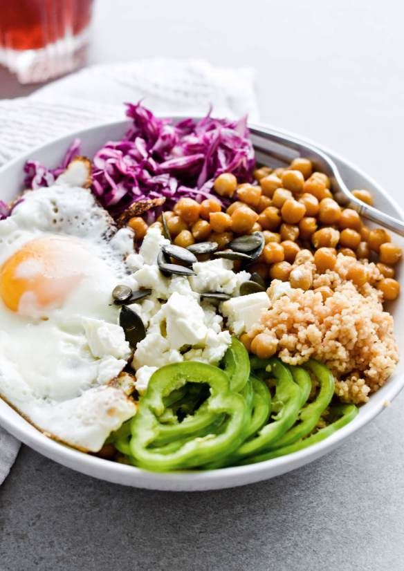 Crispy fried egg cabbage couscous bowl with crispy chickpeas, feta cheese, pumpkin seeds and peppers. So good! And the best red cabbage salad ever. Made fairly quickly. | mitzyathome.com