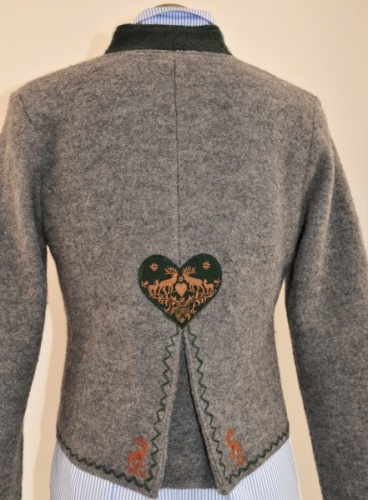 Walk jacket, stand-up collar, lapel collar and placket edged in colors. Slits at front seams, elaborate decorative embroidery, antler buttons. Spring crease in the lower back, Heart application with deer stick in the middle of the back. colors: light gray/ fir Imported from Austria.