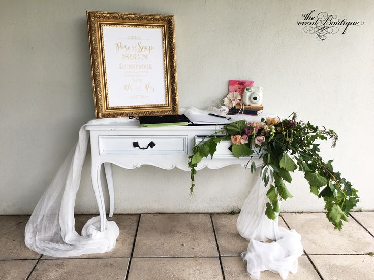 Our white dresser styled as a polaroid guest station with romantic muslin, foliage & florals spilling from the draw, with ornate gold framed 'pose, shoot & snap sign'.