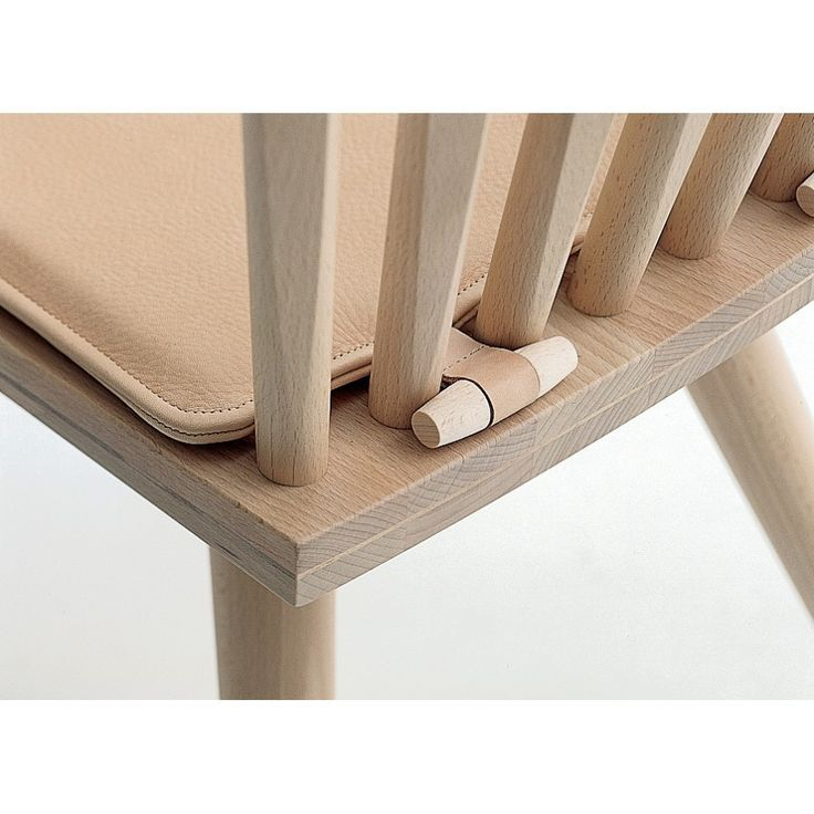 Add a wood toggle button with a strip of fabric and you will keep the cushion in place
