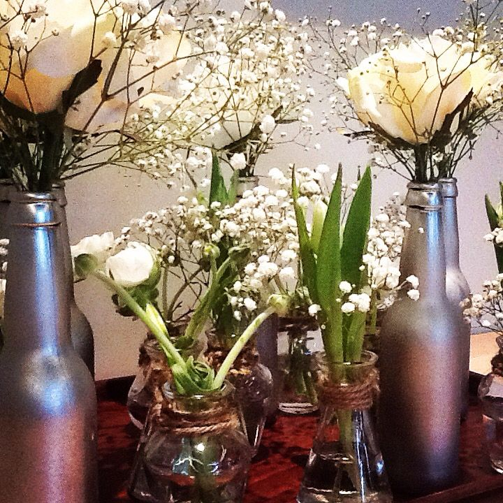 Centerpiece items waiting to be placed. Beer bottles sprayed with silver and clear vases combined