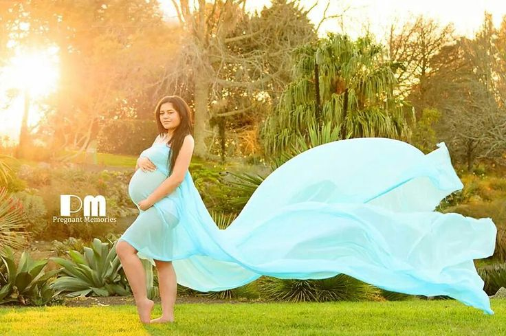 Maternity photo with blue flowing fabric material in the wind beautiful pregnancy pose