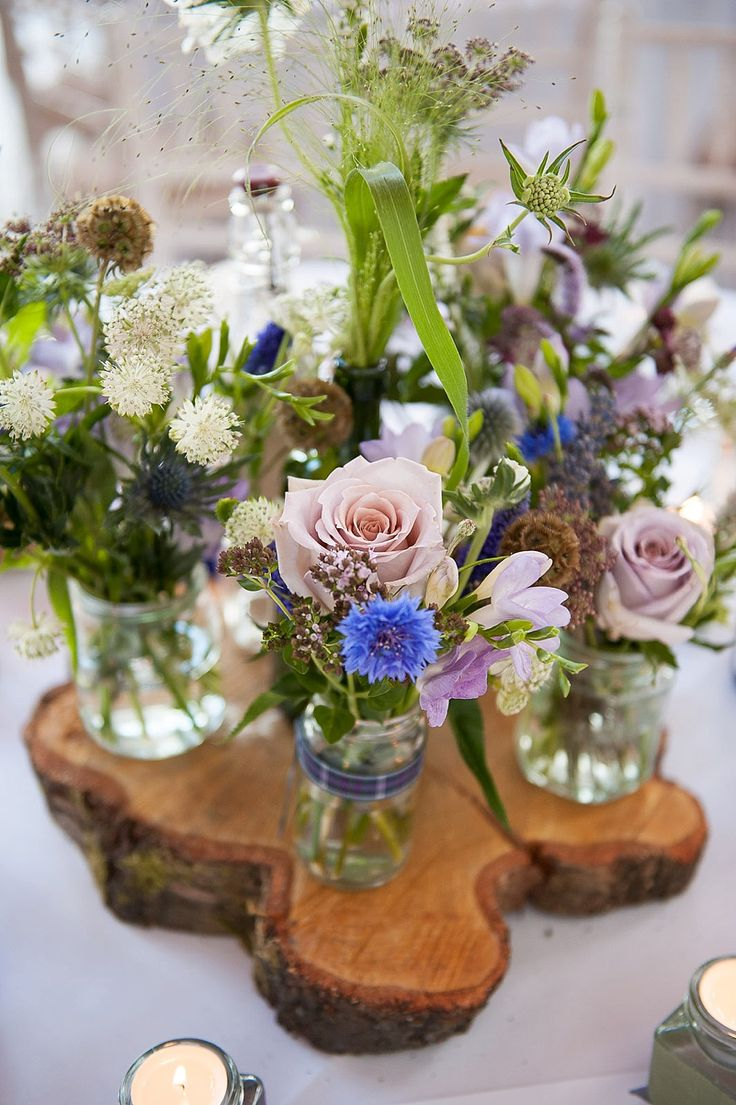 Rustic floral centre pieces in jars with wild flower lilac & blue stems - Image by Fiona Kelly - Annasul Y Wedding Gown And No 1 By Jenny Packham Bridesmaids For A Rustic Wedding At The Thames Rowing Club With Groom In Kilt And A Touch Of Tartan Theme