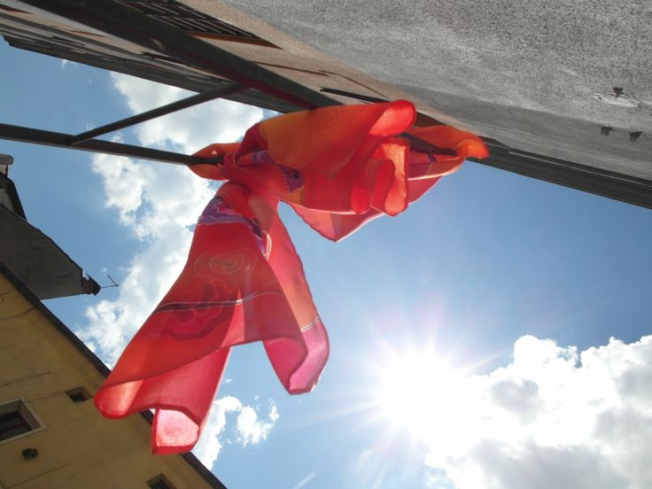 Red silk scarf, purple roses on orange and red background. I displayed it on iron rack against summer sky. Hand painted by SilkAgathe.