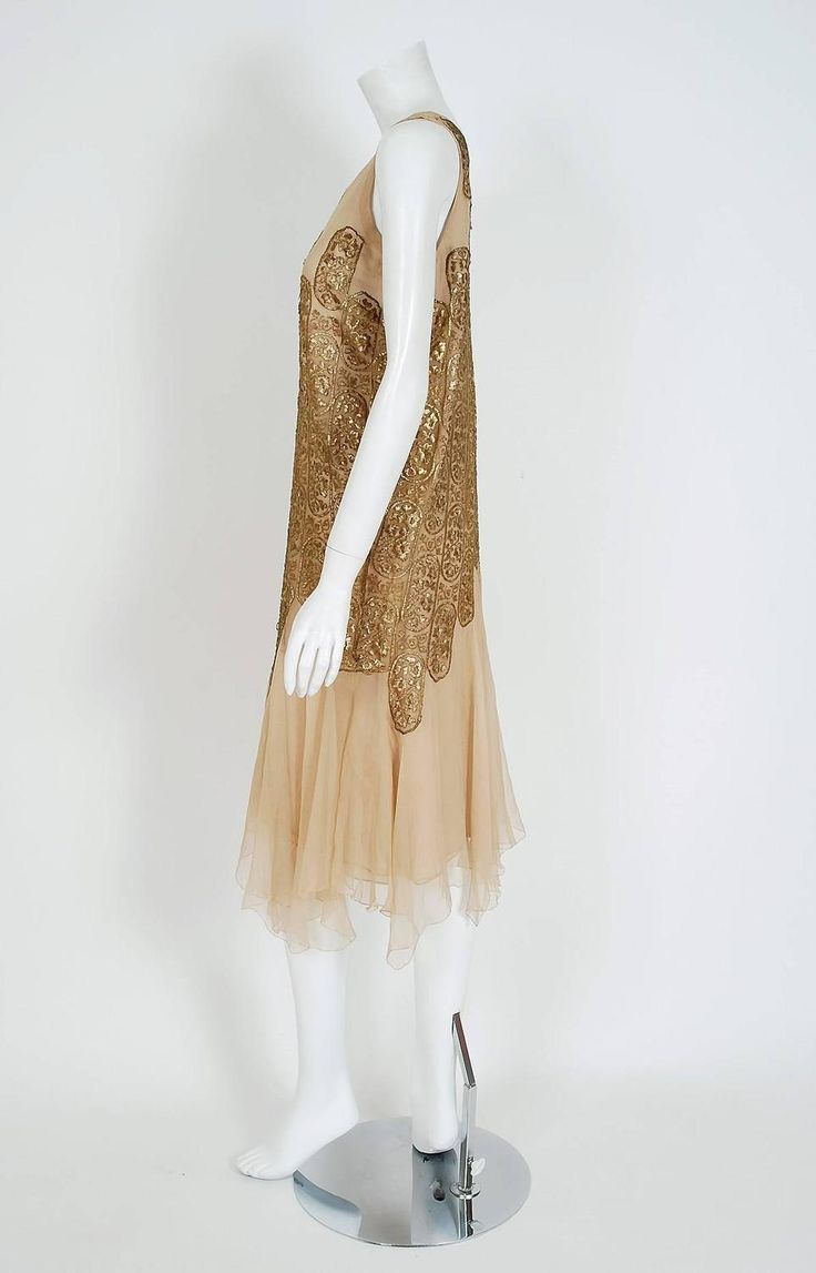 Evening dress 1925 Elspeth Champcommunal metallic gold-lame and champagne silk-chiffon dress. The lame has a floral embroidered pattern. The dress has layered handkerchief skirting and scalloped art-deco work. Garment slips over head with no additional closures. Elspeth Champcommunal was a British fashion designer and the first editor of Vogue in Britain. She was influential as a designer in her own right in Paris, later taking on the role of chief designer of Worth Side 3