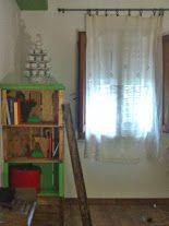 laterale di uno spazio realizzato con cassette della frutta adibito ad armadio. Piccola scala appoggiata in legno.