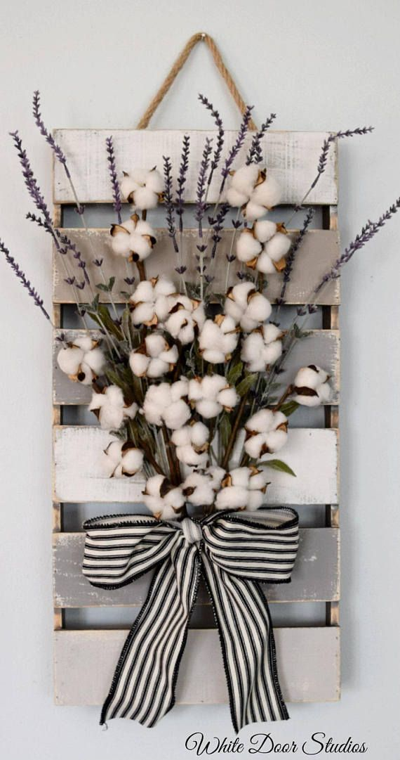 Farmhouse chic in an unexpected way. Faux lavender, rustic cotton stems and a rustic wood pallet come together to create a warm and inviting piece perfect for any room of your home. An original design from White Door Studios. Hand stained, painted and assembled just for you. A