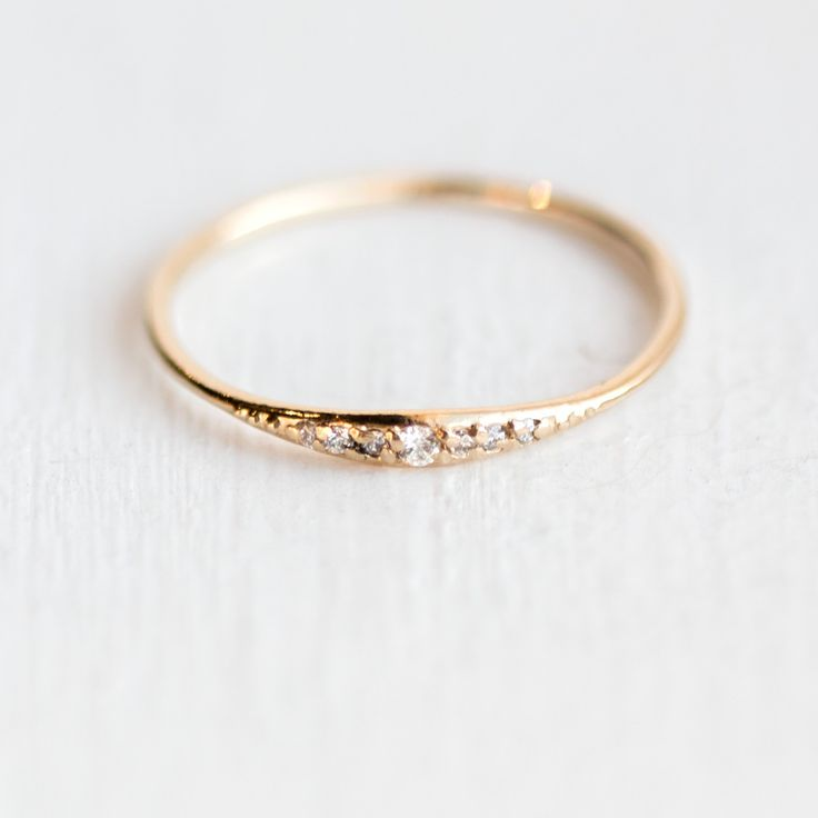 This delicate little diamond ring would make a great addition to any stacking ring set. This piece is simple and sweet, and can be customized in your choice of 14k gold metal color and finish. We ha