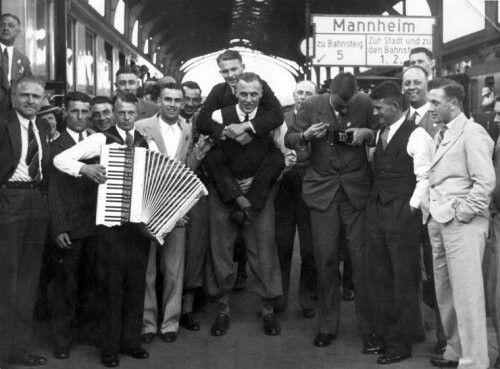 Voetbal. Wereldkampioenschap (WK) 1934 in Italië. Op het station van Mannheim stappen de voetballers even uit om de benen te strekken vlnr, Leo Halle, Sjef van Run, Puck van Heel, accordeonist Jaap Mol,(daarachter) Adri van Male, Kees Mijnders, Bep Bakhuys, Wim Lagendaal, (op zijn rug) Frank Wels, (met camera) Gejus van der Meulen, Kick Smit, Karel Lotsy, en Leen Vente. Mannheim Mei 1934 .