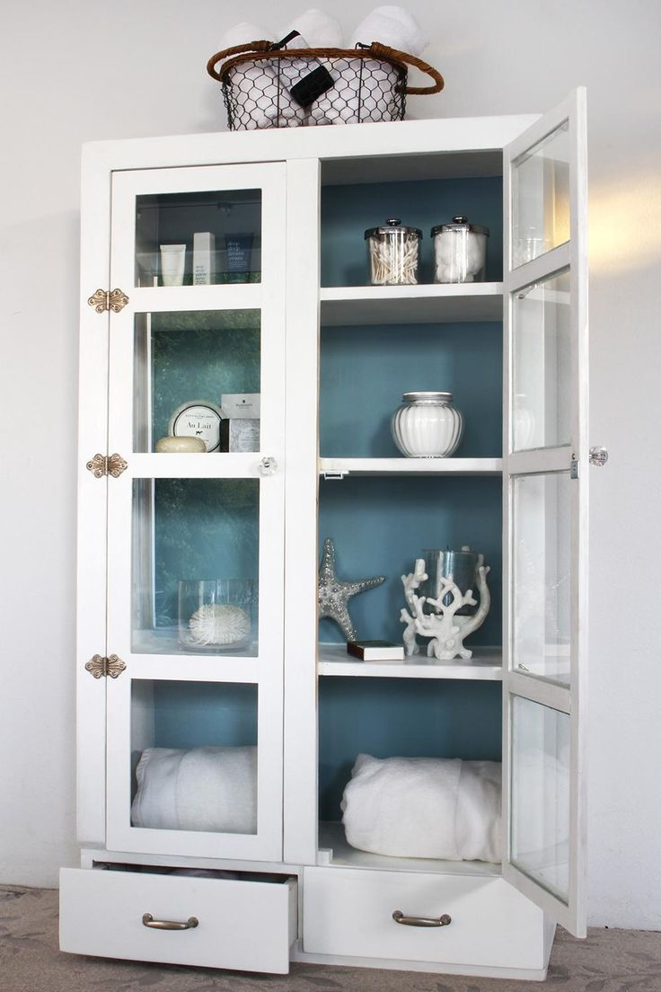"""This one of a kind solid wood cabinet newly painted white with a custom blue paint finish inside.  Probably from the 40's or 50's... this hand made cabinet was possibly a jelly cupboard originally.  We added new doors since the original doors were slightly warped & also  placed individual glass inserts in each window.  The """"vintage butterfly hinges"""" are original to the cabinet.  This piece would make great storage in a bathroom, kitchen, bedroom or any room that wants to..."""