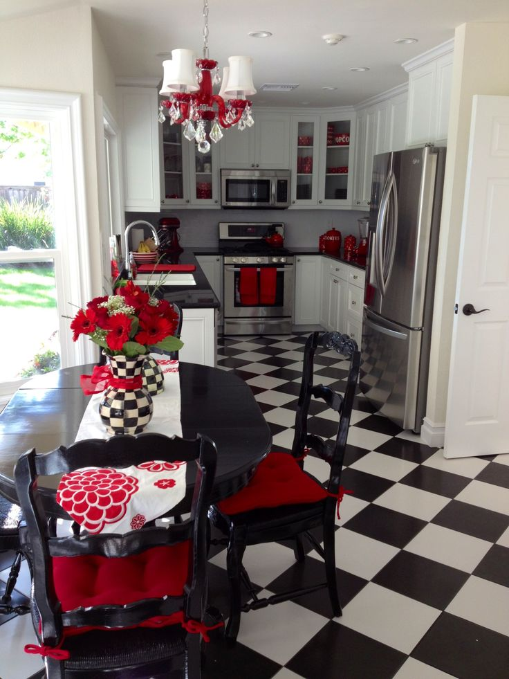 My fun and unique black and white kitchen with red accents and a  checkerboard floor.