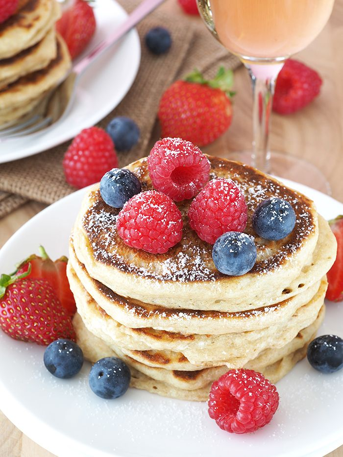 A tall stack of soft and fluffy champagne pancakes topped with champagne-spiked raspberry sauce. These pancakes are made extra fluffy using Greek Yogurt. Via @BreakfastDrama