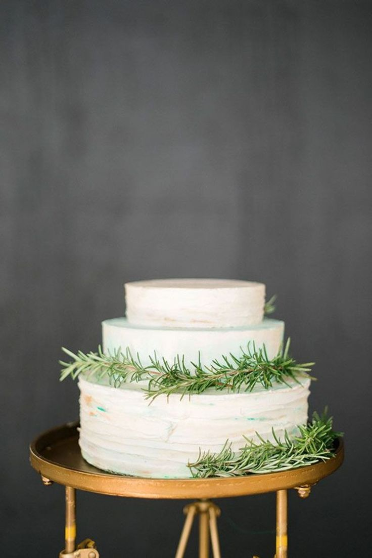 Simple, white 3-tiered wedding cake with garlands of rosemary & a gold cake stand.